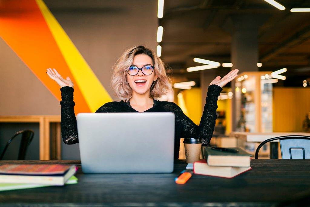 funcionária com o notebook no escritório - melhorando o engajamento