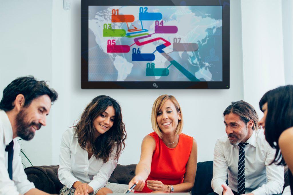 funcionários em reunião com TV corporativa ao fundo