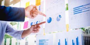 Executivos apontado para papéis com dados sobre a comunicação interna nas empresas